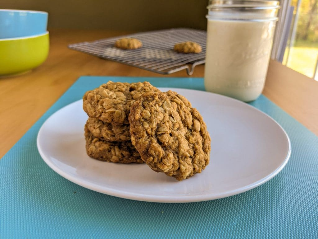 Plate of vegan oatmeal cookies next to a glass of cold almond milk