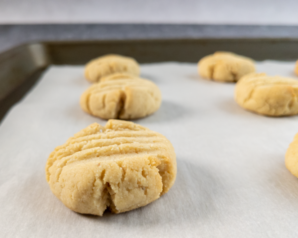 Vegan almond cookies fresh out of the oven should be allowed to cool on the baking sheet to firm up.